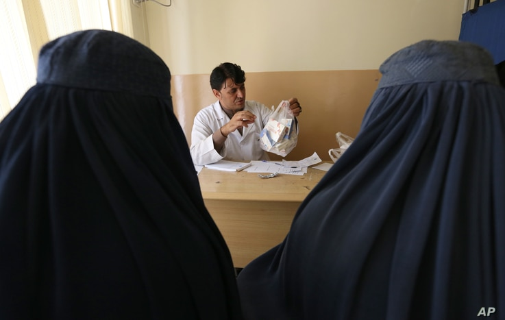 FILE - An Afghan mental health doctor, center, talks with patients in the Mental Health and Drug Addicts' Hospital in Kabul, Afghanistan, July 17, 2016.