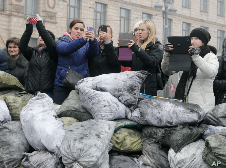 Tourists make photos of barricades in front of riot police in central Kiev, the epicenter of the country's current unrest, Ukraine, Sunday, Feb. 9, 2014. Ukraine's security agency on Sunday warned of a heightened risk of terrorism, including from the