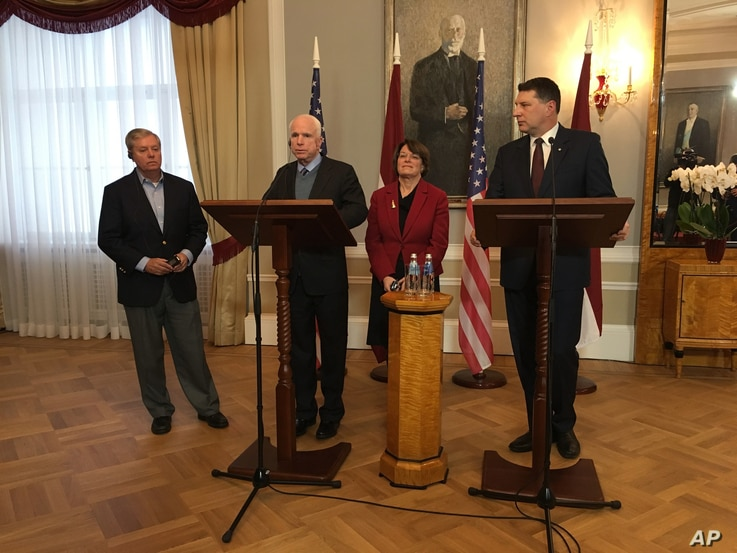 Latvian President Raimonds Vejonis, right, looks at  US Sen. John McCain centre left, during a press conference,  Wednesday, Dec. 28, 2016 in Riga, Latvia, while Lindsey Graham, and Amy Klobuchar stand in the background.