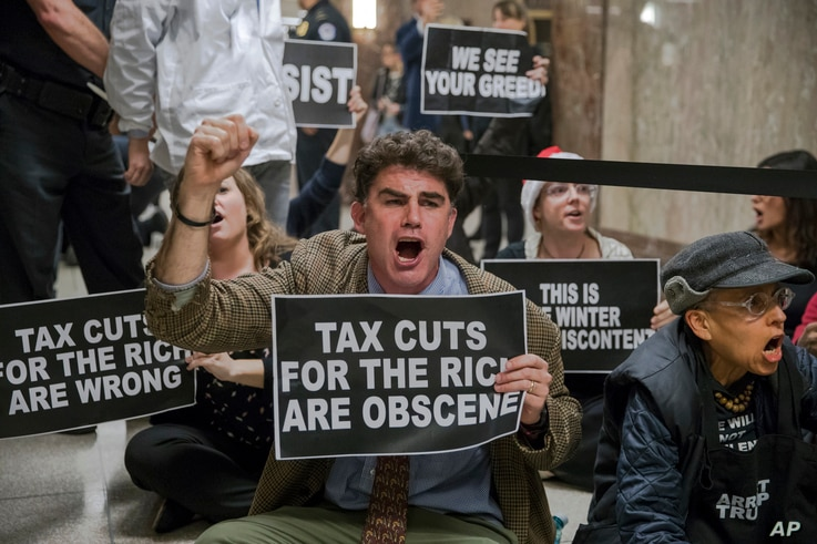 Protesters shout their disapproval of the Republican tax bill outside the Senate Budget Committee hearing room on Capitol Hill in Washington, Nov. 28, 2017.