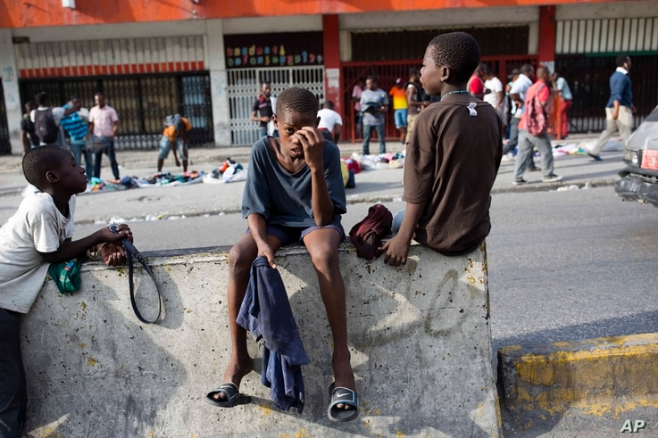 Street boys await vehicles to offer their cleaning jobs in Port-au-Prince, Haiti, June 12, 2017.