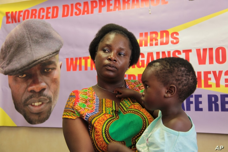 FILE - Sheffra Dzamara, wife of activist Itai Dzamara, holds her 2-year-old daughter and speaks to The Associated Press in Harare, March 8, 2016. Dzamara was pleading for the return of her activist husband, abducted by suspected state security agents
