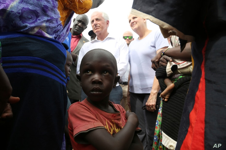 A child looks up while U.S. Sen. Bob Corker, center left, speaks to recent refugees from South Sudan at a registration center in Bidi Bidi, Uganda, April 14, 2017.