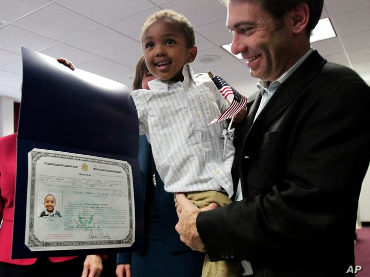 FILE - Aaron Lieberman holds his son Theodore, 2, adopted from Ethiopia, as he shows his citizenship certificate, during the U.S. Citizenship and Immigration Services (USCIS) Adoption Day ceremony on Nov. 18, 2010, in New York.