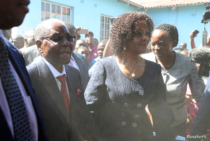 FILE - Dust engulfs former Zimbabwean president Robert Mugabe, accompanied by his wife Grace, as he arrives to vote in the general elections in Harare, Zimbabwe, July 30, 2018.