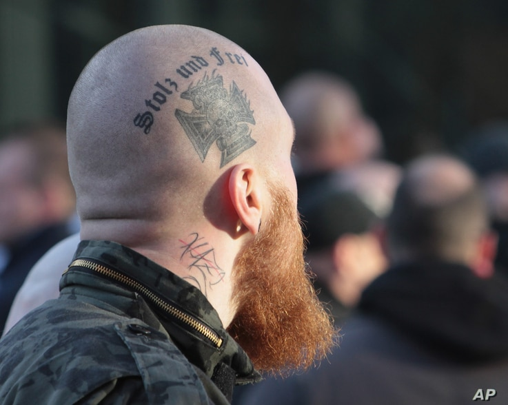 FILE - A right-wing demonstrator with a tattoo reading: 'Proud and Free'  marches in Cologne, Germany, Jan. 9, 2016.
