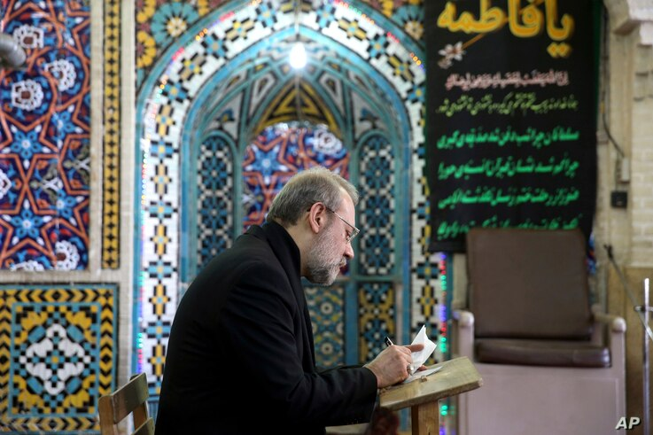 Iran's Parliament Speaker Ali Larijani votes in the parliamentary and Experts Assembly elections at a polling station in Qom, 125 kilometers (78 miles) south of the capital Tehran, Iran, Feb. 26, 2016.