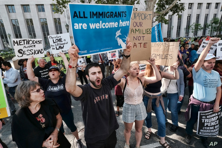 Protesters carry signs and chant slogans in front of Federal Courthouse in Los Angeles, June 26, 2018.