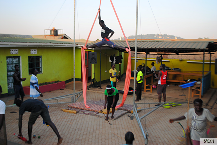One of the Uganda's Hiccup Circus's senior aerialists practices his splits while jugglers and acrobats gather around to watch. Often found instructing aspiring aerialists, he is seen as one of the most fearless in the troupe. (Elizabeth Paulat/VOA)