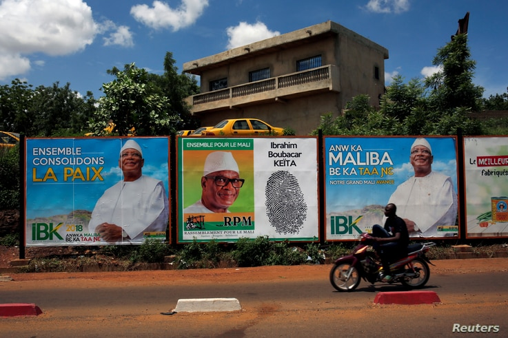 A man rides his motorcycle next to the electoral bilibaords of Ibrahim Boubacar Keita, the Malian president and leader of RPM (Rassemblement Pour le Mali), in Bamako, Mali July 23, 2018.