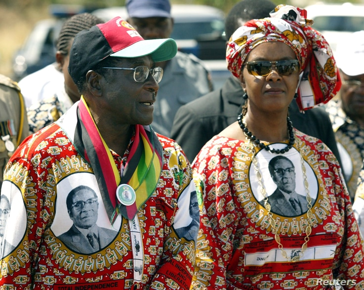 FILE - Zimbabwe President Robert Mugabe and his wife Grace arrive at an election rally in Chivu, 150 Km's south of the capital Harare, March 28, 2005.