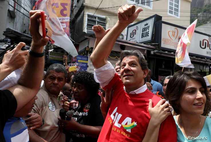 FILE PHOTO: Workers Party presidential candidate Fernando Haddad waves next to his vice presidential candidate Manuela d'Avila at the Rocinha slum in Rio de Janeiro, Brazil Sept. 14, 2018.