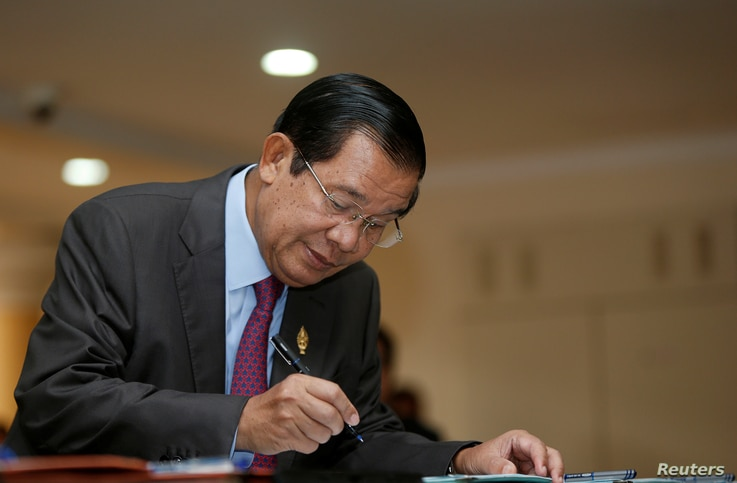 Cambodia's Prime Minister Hun Sen signs a register as he arrives before a plenary session at the National Assembly of Cambodia, in central Phnom Penh, Oct. 12, 2017.