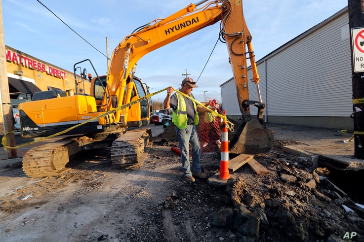 Workers fix a sewer main below the sidewalk in Mid City New Orleans, Jan. 31, 2018.  New Orleans' mayor says President Donald Trump's infrastructure proposal puts the onus on cities and states to raise taxes and fees to pay for the improvements. ...