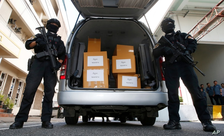 FILE - Thai policemen stand guard next to 100 kilograms of seized marijuana before a news conference Bangkok, Thailand, Tuesday, Sept. 25, 2018.