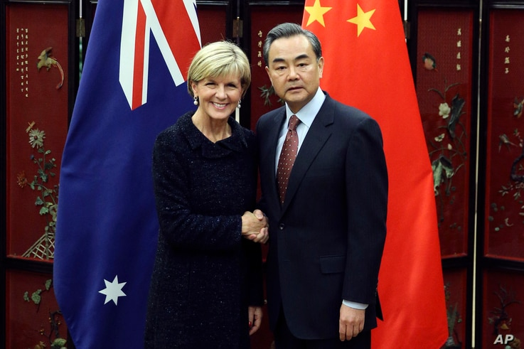 Australian Foreign Minister Julie Bishop, left, and Chinese Foreign Minister Wang Yi pose for photographers as she arrives for a meeting at the Ministry of Foreign Affairs in Beijing, Wednesday, Feb. 17, 2016.