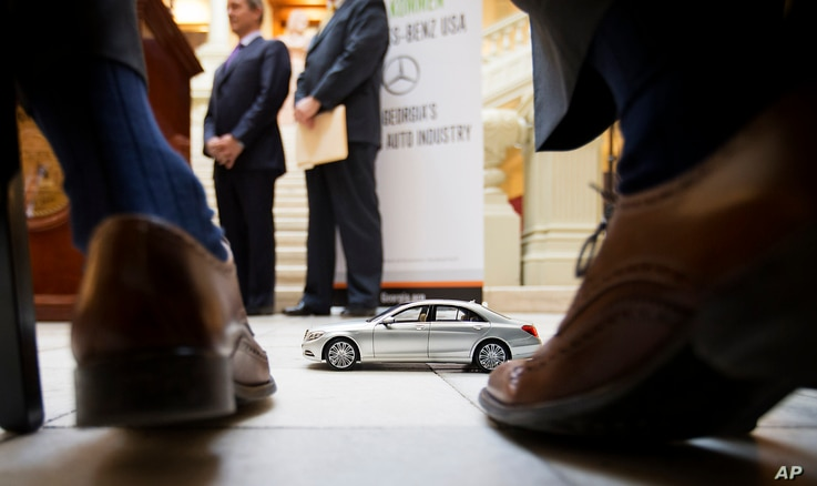 FILE- A Mercedes-Benz model sits in front of Robert Moran, director of communications for Mercedes-Benz USA, during a ceremony announcing the company's relocation of its U.S. corporate headquarters to the metro Atlanta city of Sandy Springs, Feb. 3, ...