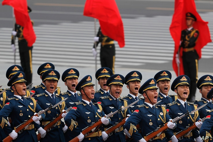 Members of an honor guard shout as they march in formation during a welcome ceremony for visiting U.S. President Donald Trump outside the Great Hall of the People in Beijing, Nov. 9, 2017.
