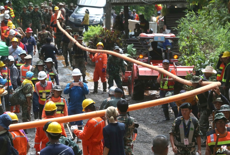 Rescuer carry water pipe makes their way up at the entrance to a cave complex where 12 boys and their soccer coach were trapped inside when heavy rains flooded the cave, in Mae Sai, Chiang Rai province, in northern Thailand, July 4, 2018.