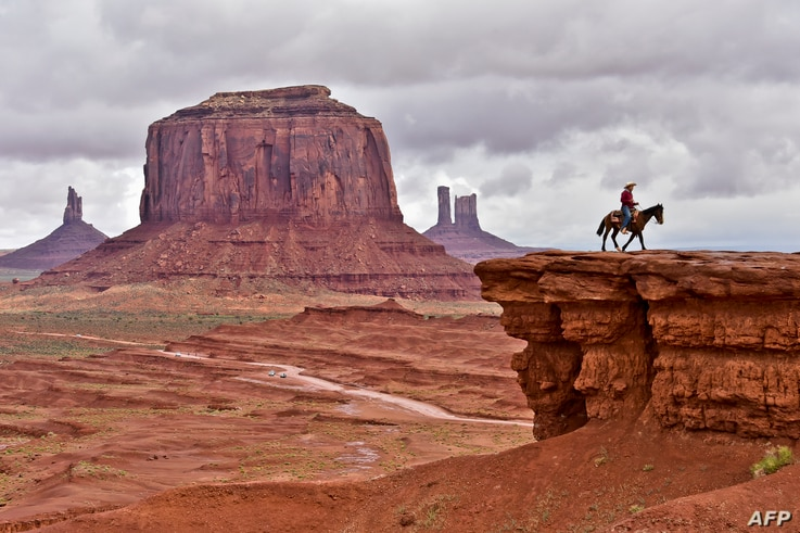 A Navajo man on a horse poses for tourists in front of the Merrick Butte in Monument Valley Navajo Tribal Park, Utah, on May 16, 2015. AFP PHOTO/MLADEN ANTONOV