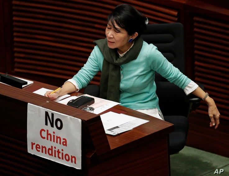 FILE - A lawmaker displays a placard to protest an extradition law at the Legislative Council, in Hong Kong, April 3, 2019.
