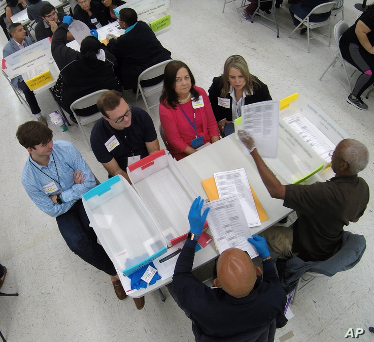 Workers at the Broward County Supervisor of Elections office, foreground, show Republican Democrat observers ballots during a hand recount, Friday, Nov. 16, 2018, in Lauderhill, Florida.