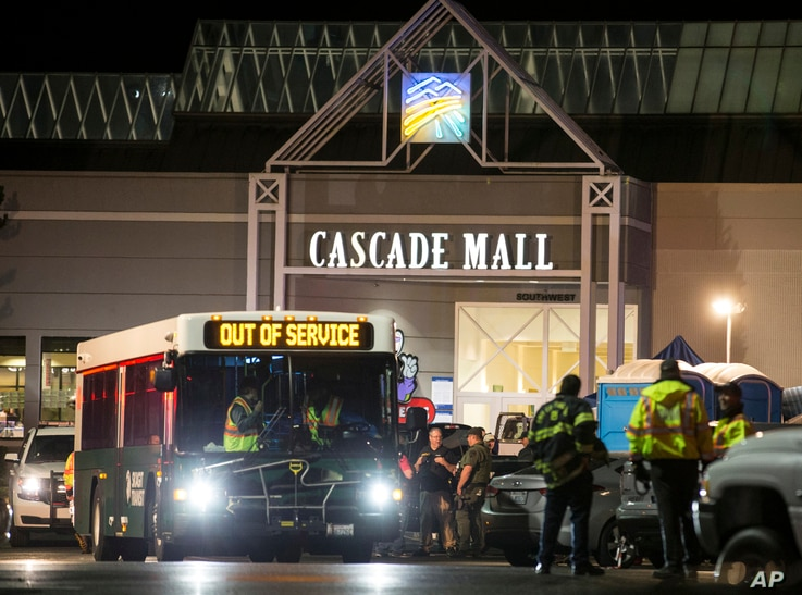 Emergency personnel stand in front of an entrance to the Cascade Mall at the scene of a shooting where several people were killed, Sept. 23, 2016, in Burlington, Washington.