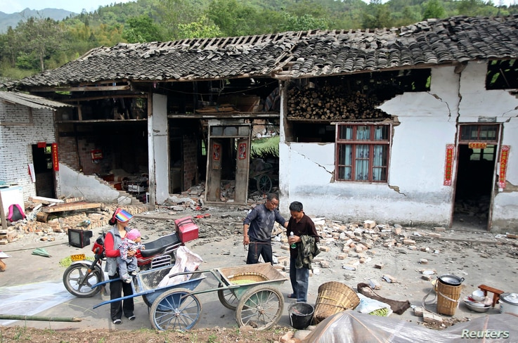 People stand outside a damaged house after a strong 6.6 magnitude earthquake hit, at Longmen village, Lushan county, Ya'an, Sichuan province, April 20, 2013.