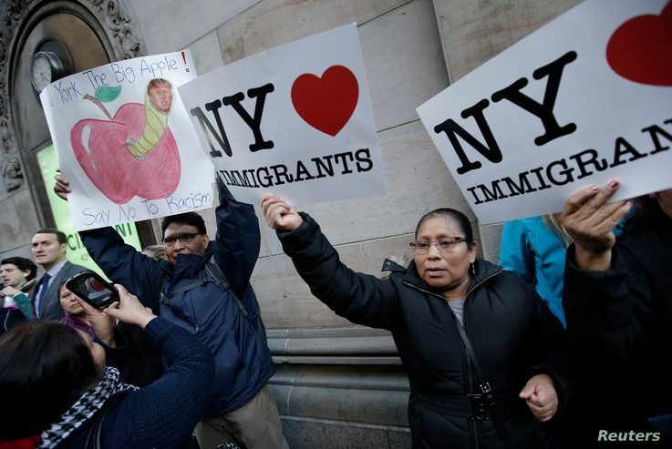 FILE - Demonstrators hold pro-immigration signs during a protest against Republican U.S. presidential candidate Donald Trump in midtown Manhattan in New York City, April 14, 2016.