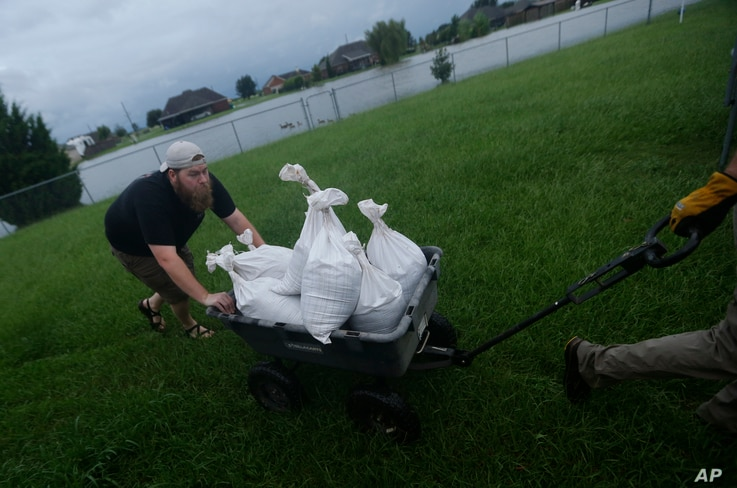 Cody McLemore pushes a wagon filled with sandbags as he fortifies his house in the flooded Clearfield Farm subdivision, in anticipation of more flooding from Tropical Storm Harvey, in Lake Charles, La., Aug. 29, 2017.