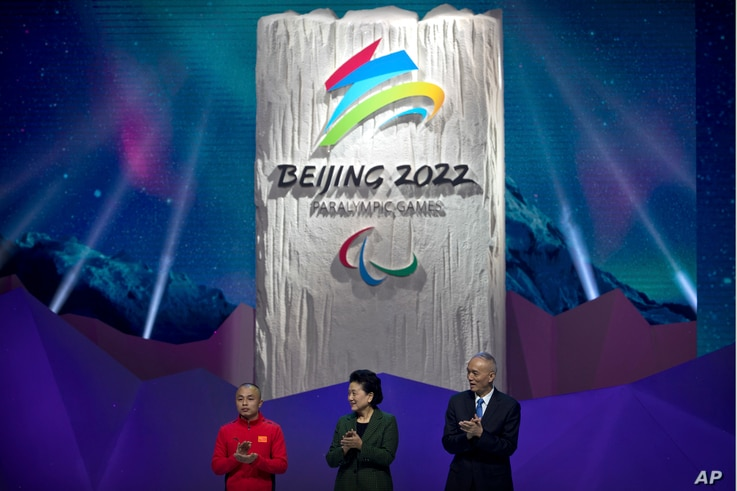 FILE - From left, 2014 Paralympic curling competitor Zhang Qiang of China, Chinese Vice Premier Liu Yandong, and Can Qi, Beijing 2022 Organizing Committee Chairman and Communist Party Secretary for Beijing, applaud as the emblem for the 2022 Beijing ...
