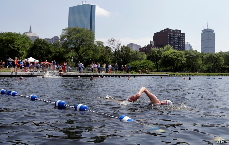 """People swim in the Charles River during the """"City Splash"""" event, July 18, 2017, in Boston."""