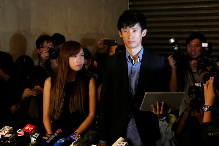 Democratically elected legislators Yau Wai-ching, left, and Baggio Leung meet journalists outside the High Court after the court disqualified them from taking office as lawmakers in Hong Kong, Nov. 15, 2016.