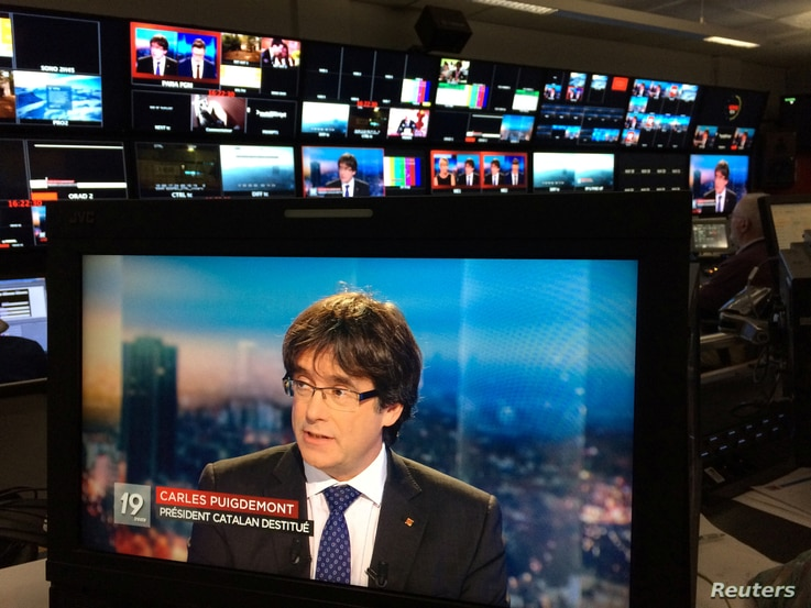 Ousted Catalan President Carles Puigdemont appears on a monitor during a live TV interview on a screen in a bar in Brussels, Belgium, Nov. 3, 2017.