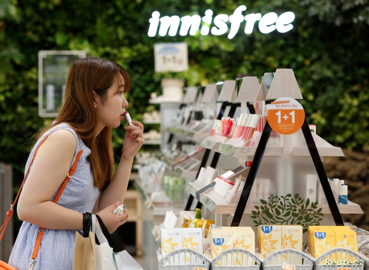 FILE - A customer tries a lipstick at a shop in central Seoul, South Korea, Aug. 6, 2013. Chinese sanctions against South Korea include restricting the import of South Korean cosmetics.