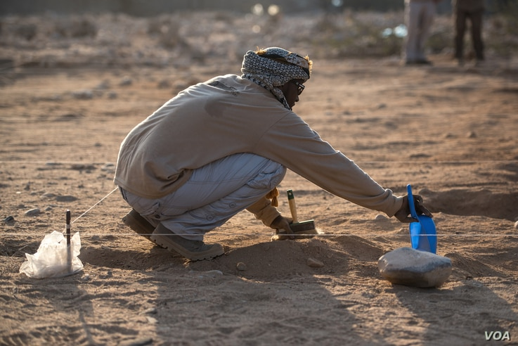 A forensic investigator brushes away soil from the top of a mass grave containing 17 bodies buried nearly 30 years ago in Berbera, Somaliland. (J. Patinkin/VOA)