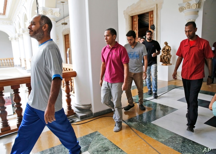 A security officer (R) escorts a group of unidentified, recently released political prisoners to a meeting with a truth commission at the Venezuelan Foreign Ministry, in Caracas, Venezuela, June 1, 2018.