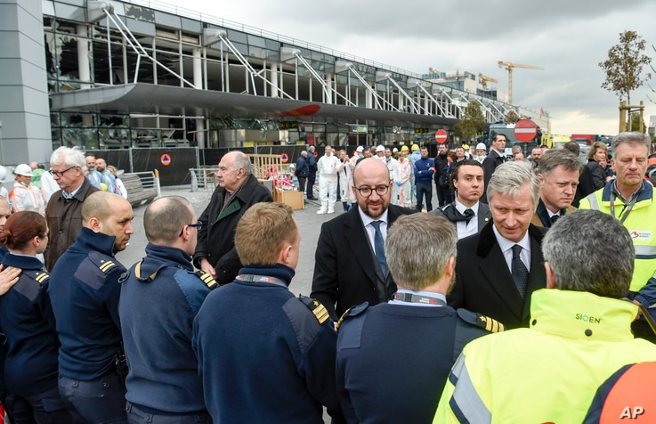 The Belgian Prime Minister Charles Michel, center, shakes hands with police officers and first responders in front of the damaged Zaventem Airport terminal in Brussels on March 23, 2016.