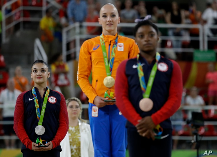 Netherlands' Sanne Wevers, center, gold, United States' Lauren Hernandez, left, silver, and United States' Simone Biles, right, stand after receiving their medals for balance beam at the 2016 Summer Olympics in Rio de Janeiro, Brazil, Aug. 15, 2016.