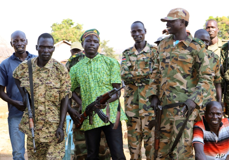 In this photo taken Jan. 6, 2019, government and opposition soldiers pose in the government barracks in Kajo Keji town, where 10 opposition soldiers were staying with the government troops in a makeshift soldier swap, in Kajo Keji county, South Sudan...
