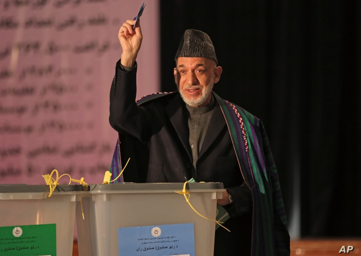 Afghan President Hamid Karzai, shows his ballot paper to the media before he casts his vote at Amani high school, near presidential palace in Kabul, Afghanistan, April 5, 2014.