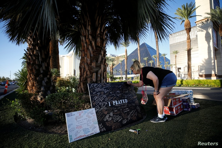 A woman writes a message on a sign at a makeshift memorial in the middle of Las Vegas Boulevard following the mass shooting in Las Vegas, Nevada, Oct. 5, 2017.