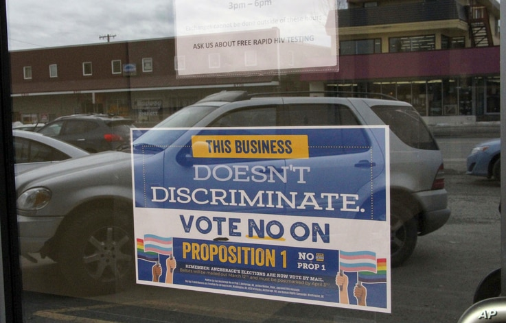 In this photo taken Monday, April 9, 2018, is a sign on a business door urging defeat of a proposition that would have rolled back protections for transgender residents in Anchorage, Alaska.