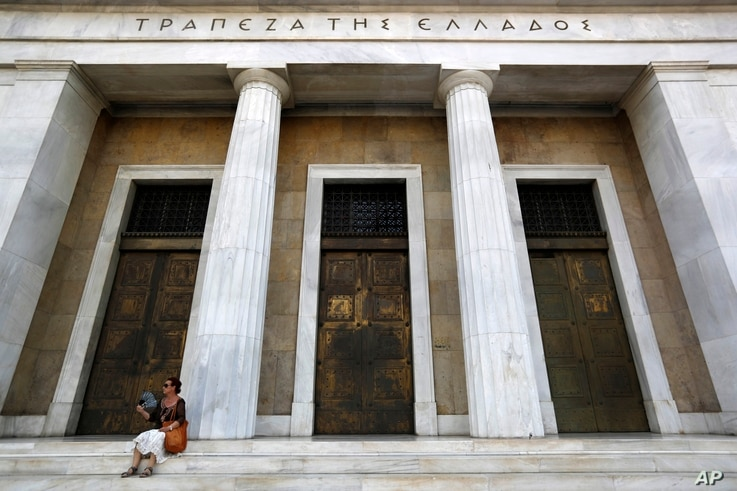 A woman uses her fan to cool down outside the Bank of Greece headquarters in Athens, July 24, 2017. Greece's bond sale on July 25, 2017, was the country's first attempt to return to international borrowing markets since a single bond issue in 2014.