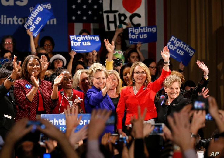 Democratic presidential candidate Hillary Clinton, center, is joined on stage by former Arizona Rep. Gabby Giffords, second from right, Leticia James, left, and New York City first lady Chirlane McCray, second from left, and others during a Women for...