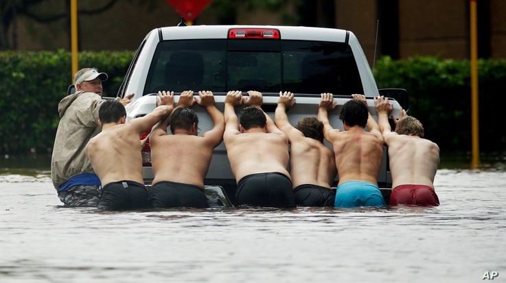 People push a stalled pickup through a flooded street in Houston, after Tropical Storm Harvey dumped heavy rains, Aug. 27, 2017.