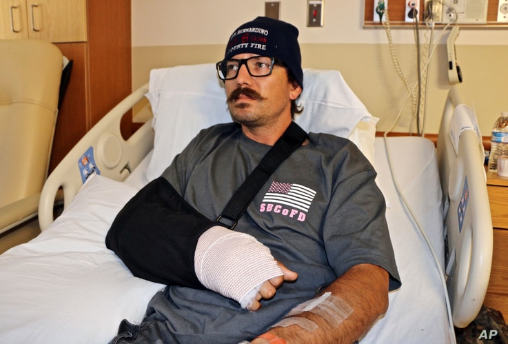 Mike Kordich, a firefighter from Rancho Cucamonga, Calif., answers questions from his hospital bed at Sunrise Hospital in Las Vegas,  Oct. 3, 2017. Kordich was giving a severely injured person CPR when he was hit by a bullet.