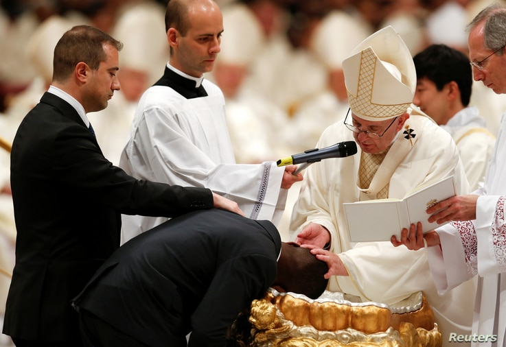 Pope Francis baptizes a man as he leads the Easter vigil Mass in Saint Peter's Basilica at the Vatican, March 31, 2018.