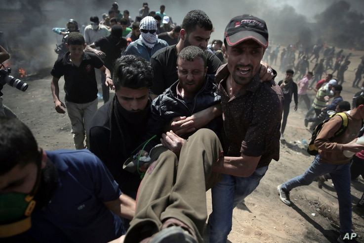 Palestinian protesters carry an injured man who was shot by Israeli troops during a protest at the Gaza Strip's border with Israel, Monday, May 14, 2018.