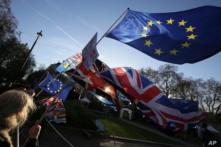 Anti-Brexit protesters wave flags outside the Houses of Parliament, in London, Dec. 12, 2018.